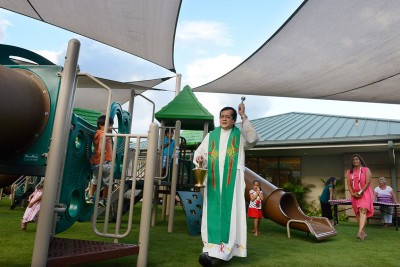 Father De Los Reyes blesses new surfacing & play project after completion.